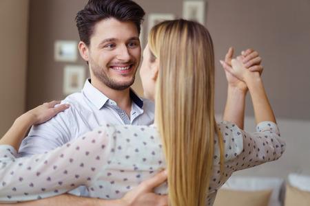 Romantisch jong paar die van een dans samen thuis met nadruk aan het glimlachende houdende van gezicht van de knappe jonge man genieten Stockfoto