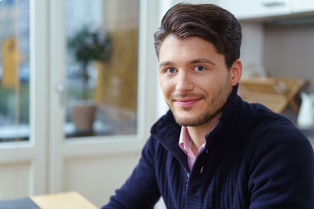 stubbly: Attractive young man with a stubbly beard sitting indoors at home looking at the camera with a friendly smile, head and shoulders close up