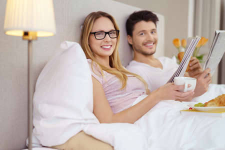 catch up: Young married couple enjoying a relaxing day having a healthy breakfast in bed as they catch up on the local news in the paper Stock Photo