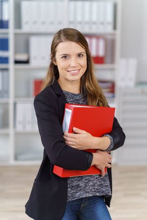 file clerks: Single cute smiling office worker in jacket, sweater and jeans holding large red binder in front of bookshelf indoors