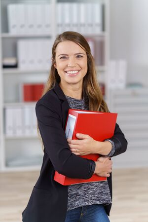 file clerks: Single happy young executive with long brown hair and black jacket standing in small office holding red binder close to her chest Stock Photo