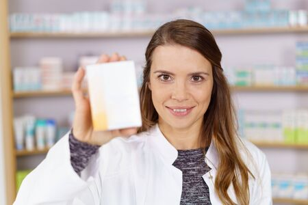 doctor holding gift: Single grinning pharmacist with white lab coat and long hair holding up an obscured box of medicine in pharmacy