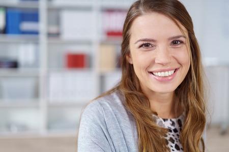 카메라를보고 사무실에서 사랑스러운 친절한 미소로 예쁜 젊은 사업가의 머리와 어깨를 닫습니다