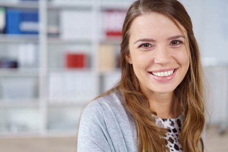 company employee: Close up head and shoulders of a pretty young businesswoman with a lovely friendly smile standing in the office looking at the camera Stock Photo