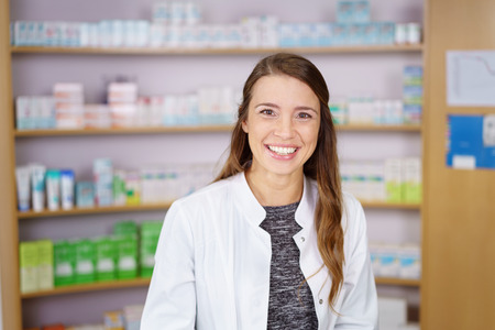 single shelf: Single smiling young adult female pharmacist in white lab jacket in front of shelf of obscured medication