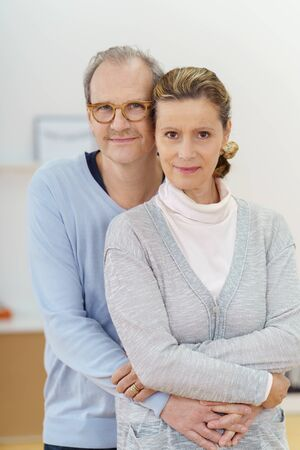 affectionate: Affectionate middle-aged couple posing arm in arm for the camera with friendly smiles, upper body standing Stock Photo