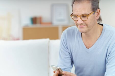 leaning forward: Close up of grinning middle aged man with mustache and eyeglasses leaning forward as he checks his cell phone