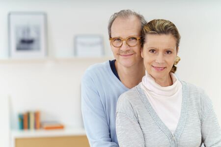 aged: Smiling happy middle aged couple posing in a close embrace lloking at the camera with friendly smiles, with copy space to the side