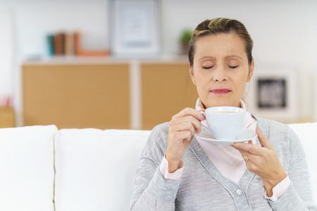 olfato: Madura en calma y con los ojos cerrados disfrutando de la fragancia de café caliente en la taza celebrada hasta la nariz mientras se está sentado en el sofá Foto de archivo