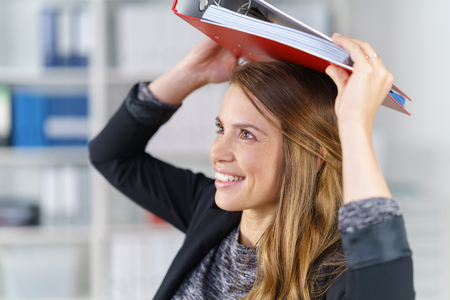 file clerks: Cute cheerful young brunette woman in black blazer holding a large red binder on top of her head Stock Photo