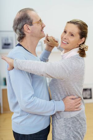 dancing house: Happy middle-aged couple relaxing dancing together at home in the living room with smiles of enjoyment