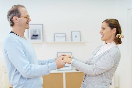 two hands: Happy playful middle-aged couple holding hands and laughing as they face each other, profile upper body view
