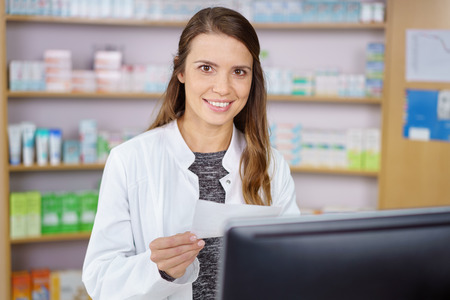 Single young pharmacy technician in long brown hair and white lab coat entering prescription order on computer with medications on shelf in background