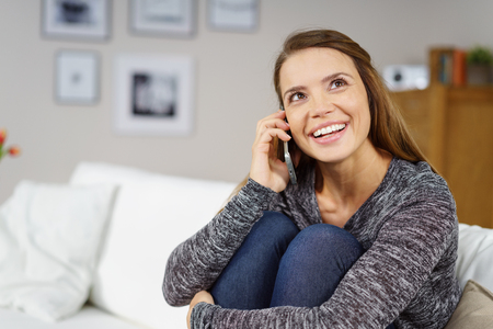 Beautiful single young adult woman in gray sweater holding knees while sitting on white sofa and talking on cell phone indoors Foto de archivo