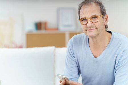 receding hairline: Copy space to side of confident middle aged man with receding hairline and mustache sitting on sofa using cell phone Stock Photo