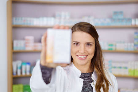 obscured: Single female pharmacist with smile and long hair holding up an obscured box of medicine in pharmacy