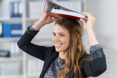 file clerks: Happy young office worker balancing a large red binder on her head with a playful smile as she stands in the office