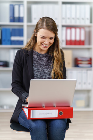 file clerks: Single cheerful female office worker in long brown hair, jeans and black blazer sitting with laptop and red binder in lap Stock Photo
