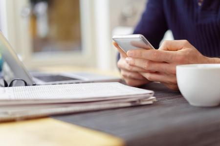 Pruebas de hombre en su teléfono móvil mientras se está sentado a la mesa en casa con un periódico abierto delante de él Foto de archivo