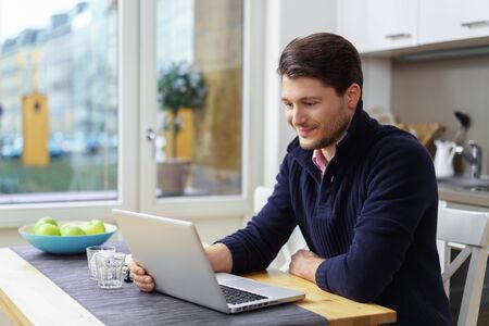 blue collar: Grinning single young man wearing blue collar sweater looking at laptop on table next to bowl of fruit in kitchen Stock Photo