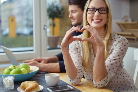 working hands: Smiling young woman gesturing a loving heart symbol with fingers while seated next to handsome man on laptop in kitchen Stock Photo