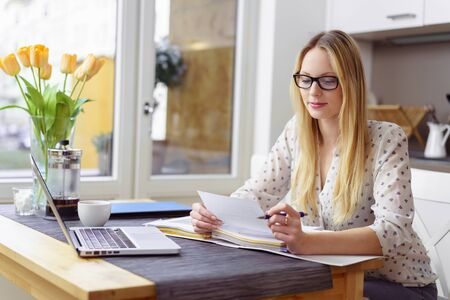 Serious young blond woman wearing eyeglasses sitting at little table with laptop and financial statements in kitchen next to bright window