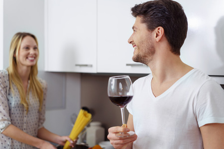 glass half full: Cheerful woman preparing pasta noodles while husband in tee shirt holds a glass half full of red wine in the kitchen Stock Photo