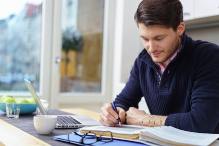 alongside: Businessman sitting at a table writing notes in an office binder with his laptop open alongside