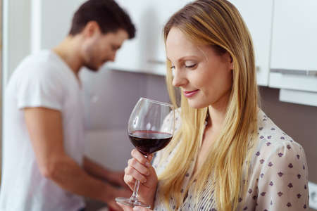 novio: Pretty young blond woman drinking red wine as her husband works at a kitchen counter in the background, profile view Foto de archivo
