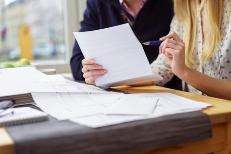 Husband and wife discussing a document together as they sit at a table in the kitchen doing paperwork balancing the books,close up of her hands pointing out something with a pen