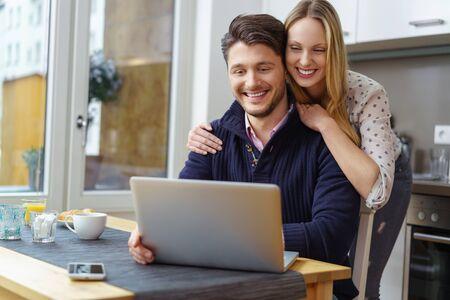 jovenes felices: Mujer rubia feliz en la blusa de puntos apoyada sobre el hombre sonriente barbudo hermoso usando la computadora portátil en la mesa de la cocina