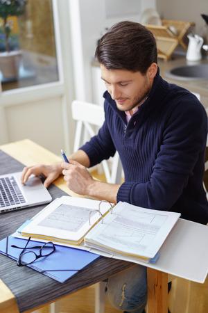 Joven adulto de sexo masculino con barba en el suéter azul que mira sobre la información en poco aglutinante sobre la mesa de madera en la cocina junto a las lentes y la carpeta