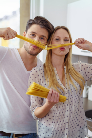 puckered: Silly young Caucasian husband and wife in their kitchen playing with straight uncooked pasta noodles near their puckered faces