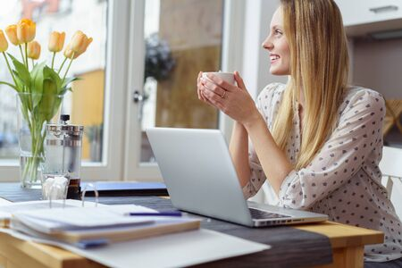 taking a break: Young woman taking a coffee break from work sitting at a table in a home office holding a cup of tea of coffee and looking out of the window with a smile Stock Photo