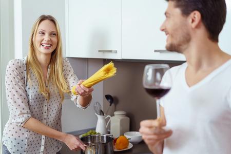 femme romantique: Rire femme blonde dans les cheveux blonds pointant un paquet de pâtes alimentaires sèches à sourire homme barbu en T-shirt, tenue, verre de vin dans la cuisine