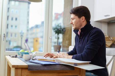 worker man: Young bearded adult male in blue sweater looking over financial ledger on little wooden table in kitchen with large window
