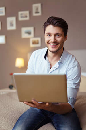 businessman working at his computer: Attractive businessman working on his laptop at home as he relaxes on a bed balancing the computer on his arm