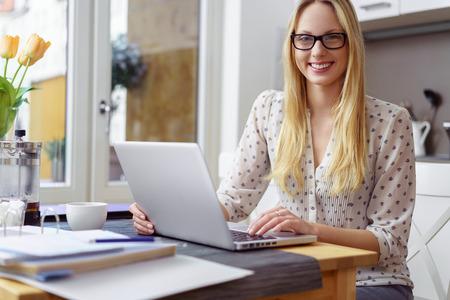 Single doordachte jonge blonde vrouw in brillen en polka dot blouse met laptop en een omblad van formulieren op tafel in de keuken Stockfoto