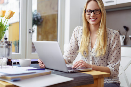 Single thoughtful young blond woman in eyeglasses and polka dot blouse with laptop and binder of forms on table in kitchen