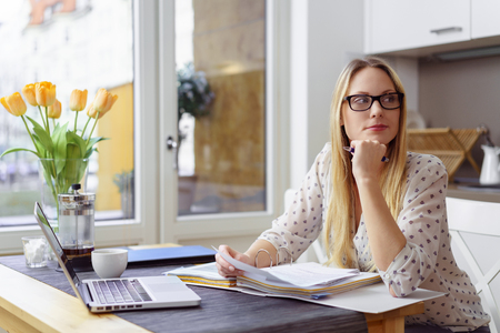 Pensive young blond woman wearing eyeglasses looking away while sitting at little table with laptop and financial statements in kitchen next to bright window Foto de archivo