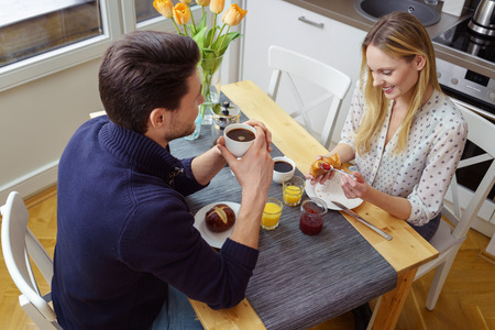 young wife: High angle view of attractive young husband and wife eating rolls and drinking orange juice or coffee for breakfast at kitchen table indoors