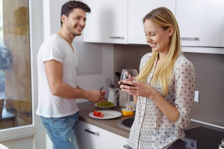 polka dotted: Happy man preparing food on plate while smiling blond woman wearing polka dotted blouse drinks wine in kitchen