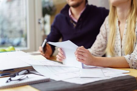 financial planning married: Woman reading a paper document as she sits at a table at home with her husband balancing the books , close up view of her hands and the paperwork
