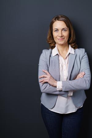 Zekere stijlvolle vrouw met een vriendelijke glimlach die zich tegen een donkere achtergrond bevindt die naar de camera kijkt met gevouwen armen, laterale kopie ruimte Stockfoto