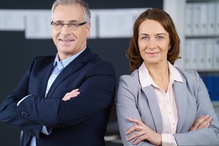 mature business man: Proud confident mature business partners, a stylish man and woman, standing back to back with folded arms smiling at the camera, office environment