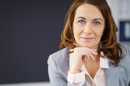 Doordachte middelbare leeftijd zakenvrouw rust haar kin op haar hand en kijkt recht in de camera, close-up kop en schouders portret met een kopie ruimte
