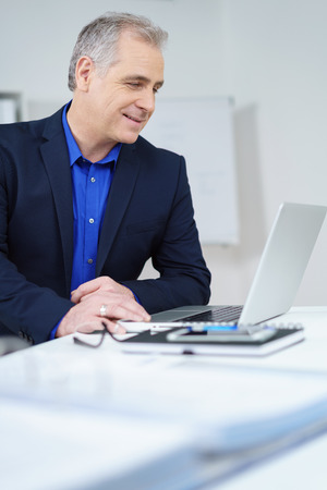 businessman suit: Attractive middle-aged businessman sitting at his desk in the office reading his laptop screen with a quiet smile of satisfaction, profile view