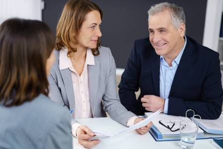 consulting room: Smiling friendly businessman in a meeting with two female colleagues sitting together at a table in the office discussing a document