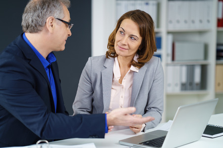 explains: Businesswoman in a meeting with a colleague listening attentively as he explains something to her as they sit together at a laptop Stock Photo