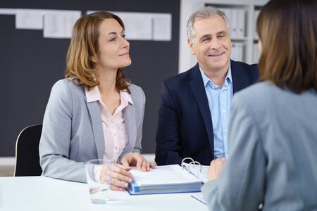 consulting business: Business partners or team in a meeting sitting together around an office table discussing paperwork, focus to a smiling middle aged man and woman Stock Photo